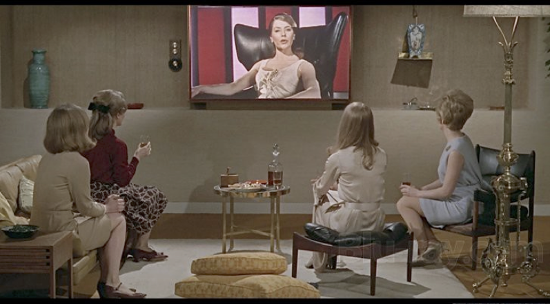 "Image 5. Women sit with ""The Family,"" the euphemistic name of state-run television in this dystopian society, as depicted in Francois Truffaut's adaptation of Fahrenheit 451.xiii"